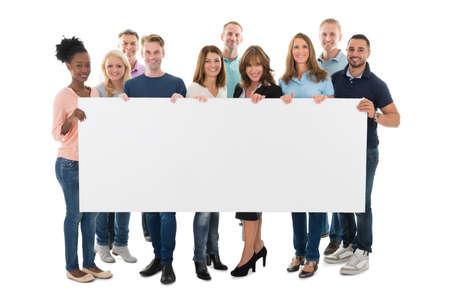 Full length portrait of confident creative business team holding blank billboard against white background Foto de archivo