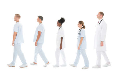 Full length side view of medical team walking in row against white background Stock Photo