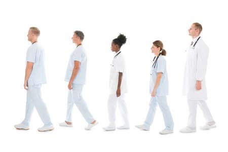 grupo de médicos: vista lateral de cuerpo entero de equipo médico pie en la fila contra el fondo blanco Foto de archivo