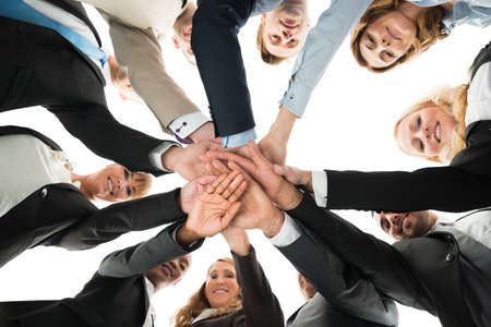 Directly below portrait of confident business team stacking hands against white background Banque d'images