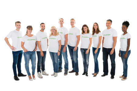 women in jeans: Full length portrait of confident volunteers standing in row against white background Stock Photo