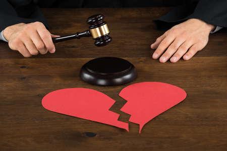 broken trust: Cropped image of divorce judge with broken heart at desk hitting gavel in courtroom