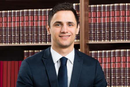 Portret van vertrouwen mannelijke advocaat staande armen gekruist tegen boekenplank in rechtszaal