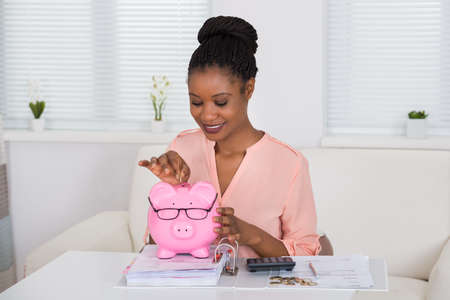 Portrait Of A Smiling African Woman Inserting Coin In Piggybank