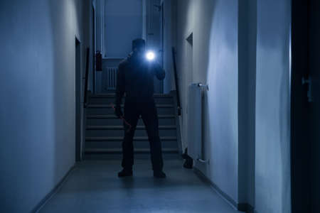 In voller Länge von Einbrecher mit Taschenlampe und Brecheisen im Büro Flur Standard-Bild
