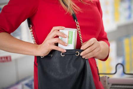 Buik van de vrouw te stelen capsule pakket bij supermarkt Stockfoto