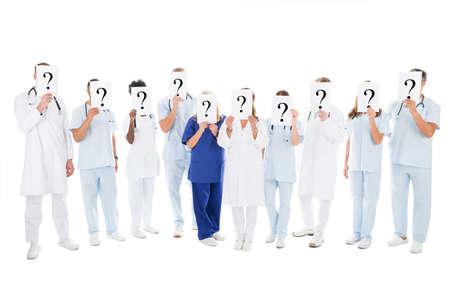preguntando: Longitud total de recubrimiento multiétnico equipo médico se enfrenta con signos signo de interrogación contra el fondo blanco