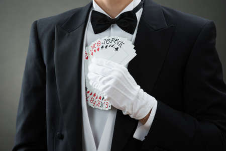 fanned: Midsection of magician putting fanned out cards in suit against gray background Stock Photo