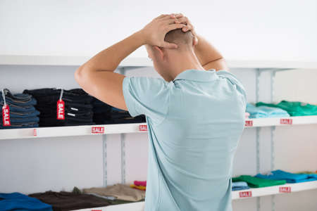 displayed: Rear view of confused man with hands on head looking at clothes displayed in store