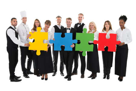 hospitality staff: Portrait of confident restaurant staff joining jigsaw pieces against white background