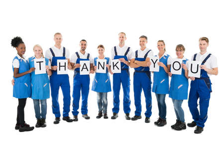 Cleaning team: Full length portrait of confident janitors holding Thank You sign against white background Stock Photo