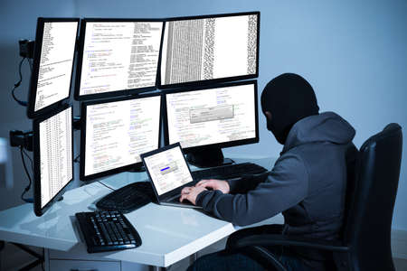 Male hacker using laptop against multiple monitors at desk in office