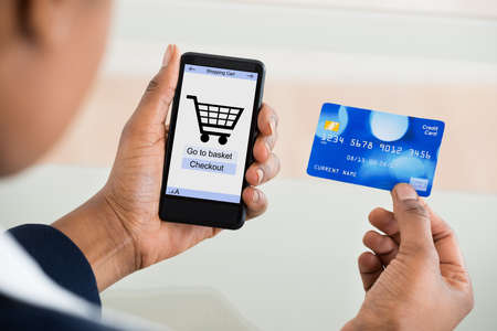 african business: Close-up Of A Woman Using Card While Shopping On Mobile Phone Stock Photo