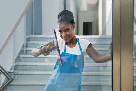 African Woman Cleaning Glass With Rubber Window Cleaner Stock Photo
