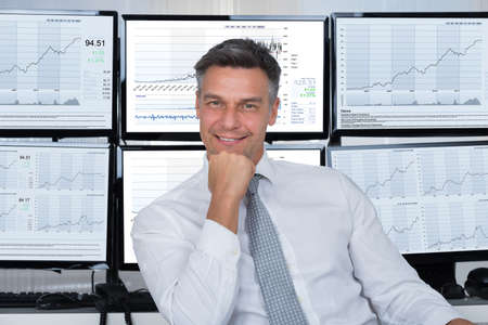 Portrait of confident stock market broker leaning on desk at office Фото со стока - 50245882