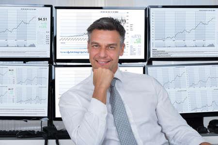 Portret pewność maklera giełdowego, opierając się na biurku w biurze