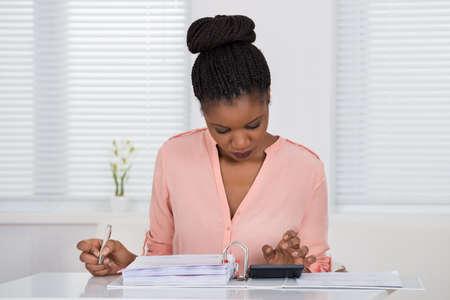 contabilidad: Mujer africana joven que calcula factura con calculadora