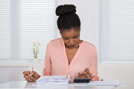 INVOICE: Young African Woman Calculating Invoice With Calculator Stock Photo