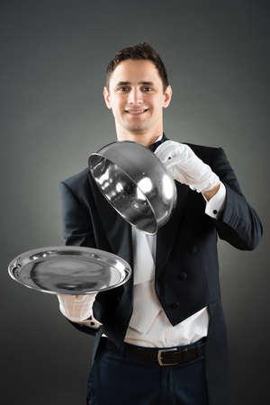 Retrato de camarero feliz celebración cloche sobre la bandeja vacía mientras está de pie contra el fondo gris