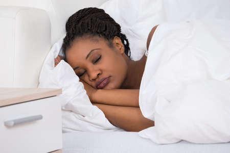 gente durmiendo: Retrato de una mujer africana joven que duerme en cama Foto de archivo