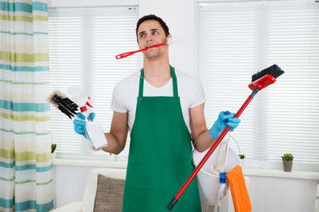 house cleaning: Overburdened cleaner holding various cleaning equipment at home