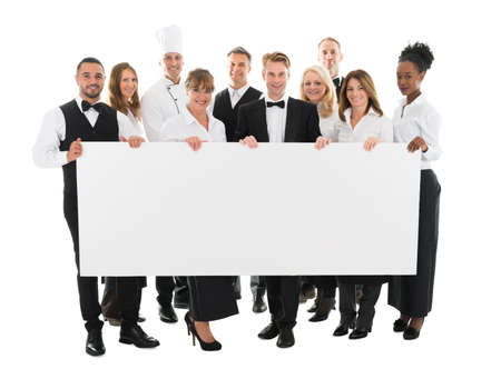 hospitality staff: Portrait of confident restaurant staff holding blank billboard against white background Stock Photo