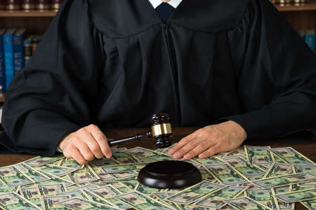 corrupt: Midsection of corrupt judge hitting gavel with banknotes spread at desk in courtroom
