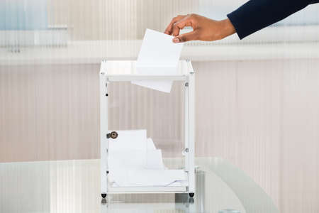 Close-up Of A Persons Hand Putting Ballot In Box