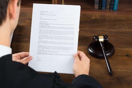 orden judicial: Vista de ángulo alto de juez de sexo masculino lectura de documentos legales en el escritorio en sala Foto de archivo