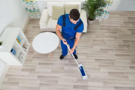 uniformes de oficina: Vista de ángulo alto del piso de madera de limpieza conserje masculino con la fregona en casa