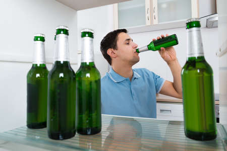 refrigerator: Young man drinking beer while standing in front of refrigerator at home Stock Photo