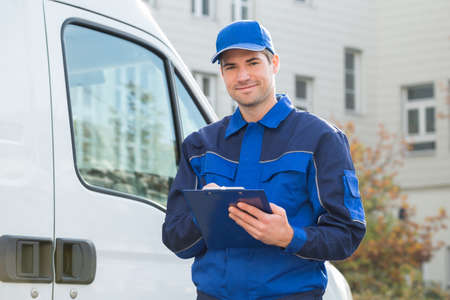 delivery: Portrait of delivery man in uniform holding clipboard by truck Stock Photo