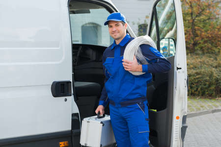 uniforms: Portrait of confident technician with cable coil and toolbox standing outside van Stock Photo
