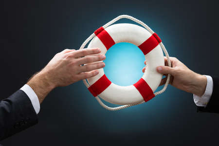 passing over: Cropped image of businessmen passing lifebuoy over blue background