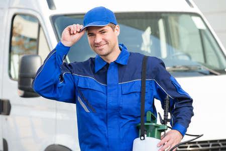 uniformes: Retrato de confianza trabajador de control de plagas que desgasta el casquillo contra el camión