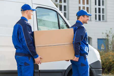 removal van: Side view of young delivery men carrying cardboard box while walking by truck Stock Photo