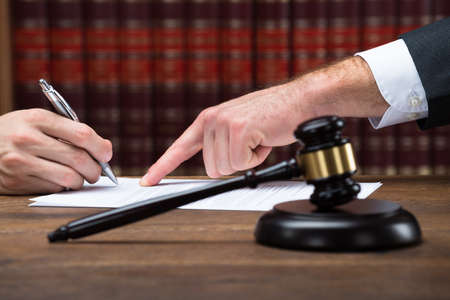 court: Cropped hand of judge assisting client to sign legal document at table in courtroom Stock Photo
