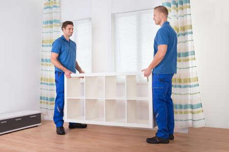 déménageurs jeunes mâles portant étagère à la maison