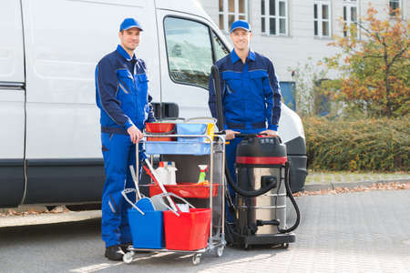 Portrait of happy janitors with cleaning equipment standing against truck Stock Photo
