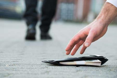 Bebouwde de hand van de zakenman het oppakken van gevallen portemonnee met geld op straat