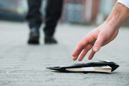 La main croisée d'un homme d'affaires ramasser un porte-monnaie déchu avec de l'argent sur la rue Banque d'images