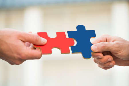 Cropped hands of businessmen joining jigsaw pieces outdoors