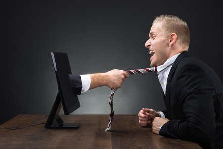 monitor de computadora: la mano del hombre de negocios que emerge del monitor de la computadora y que tira del lazo del ejecutivo en la mesa