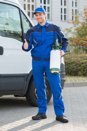 pest control: Portrait of smiling pest control worker showing thumbsup while standing by truck