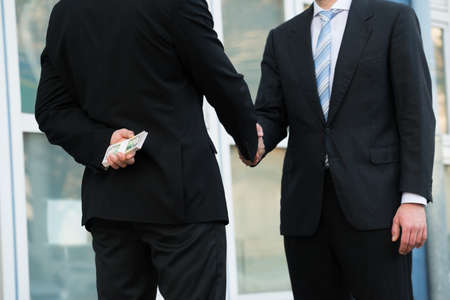 dishonest: Midsection of dishonest businessman holding dollar bundle while shaking hands with partner outdoors