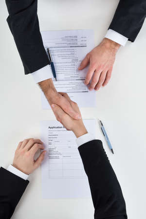 applicant: Cropped image of businessman shaking hands with male candidate at desk