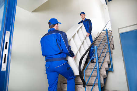 Low angle view of male movers carrying shelf while climbing steps at home 写真素材