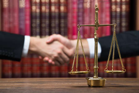 Justice scale on wooden table with judge and client shaking hands in background at courtroom