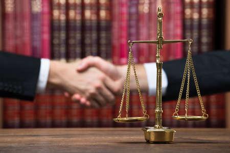 balanza justicia: Escala de la justicia en mesa de madera con el juez y el cliente dar la mano en fondo en la sala de audiencias