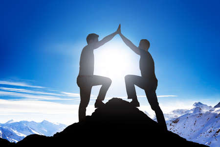 high society: Side view of silhouette male friends giving high five on mountain peak